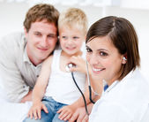 Beautiful female doctor examining a little boy with his father — Stock Photo