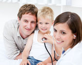 Portrait of beautiful female doctor examining a little boy with — Stock Photo