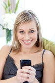 Cheerful woman sending a text sitting on a sofa — Stock Photo