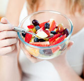 Close-up of a woman eating a fruit salad — Stok fotoğraf