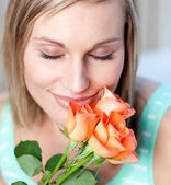 Smiling woman smelling roses — Stock Photo