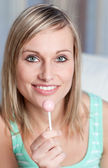 Radiant woman holding a lollipop — Stock Photo