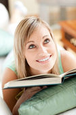 Attractive woman lying on a sofa reading a book — Stock Photo