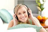 Happy blond woman listening music lying on a sofa — Stock Photo