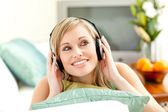 Charming blond woman listening music lying on a sofa — Stock Photo
