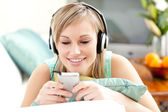 Smiling blond woman listening music lying on a sofa — Stock Photo