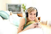 Cheerful blond woman listening music lying on a sofa — Stock Photo