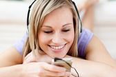 Cheerful woman listening music lying on the floor — Stock Photo