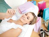 Affascinante donna in possesso di una carta di credito, circondata con ba dello shopping — Foto Stock
