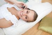 Happy woman talking on phone lying on a sofa — Stock Photo