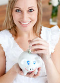 Bright woman saving money in a piggy-bank — Stock Photo