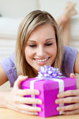 Jolly woman holding a gift — Stock Photo