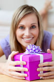 Smiling woman holding a gift — Stock Photo