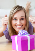 Excited woman looking at a gift lying on the floor — Stock Photo