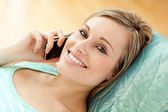 Happy young woman talking on phone lying on a sofa — Stock Photo