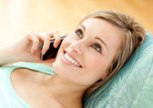 Jolly young woman talking on phone lying on a sofa — Stock Photo