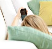 Blond woman sending a text lying on a sofa — Stock Photo