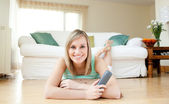 Happy young woman watching TV lying on the floor — Stock Photo