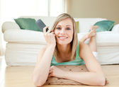 Charming young woman watching TV lying on the floor — Stock Photo