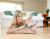 Beautiful blond woman watching TV lying on the floor — Stock Photo