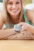 Jolly blond woman watching TV lying on the floor — Stock Photo