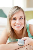 Charming blond woman watching TV lying on the floor — Stock Photo