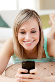 Cheerful woman sending a text lying on the floor — Stock Photo