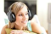 Beautful young woman listening music lying on a sofa — Stock Photo