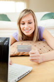 Smiling woman shopping on-line lying on the floor — Stock Photo