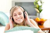 Begeistert junge frau auf einem sofa liegend musik hören — Stockfoto