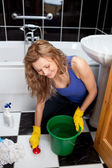 Smiling young woman cleaning bathroom's floor — Foto Stock