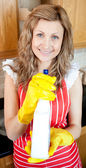 Beautiful blond woman holding a detergent spray — Stock Photo