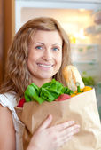 Radiant woman holding a grocery bag — Stock Photo