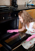Young woman cleaning the oven — Stock Photo