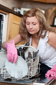 Young woman using a dishwasher — 图库照片