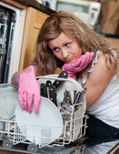 Tired young woman filing the dishwasher — Stok fotoğraf