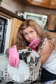 Tired blond woman filing the dishwasher — Stok fotoğraf