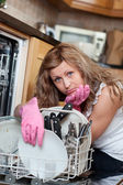Tired cute woman filing the dishwasher — Stok fotoğraf
