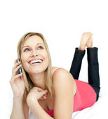 Jolly woman talking on phone lying on a bed — Stock Photo