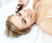 Charming woman talking on phone lying on a bed — Stock Photo