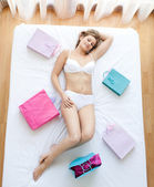 Relaxed woman lying on a bed surrounded with shopping bags — Stock Photo
