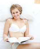 Happy woman reading a magazine lying on a bed — Stock Photo