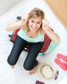 Successful woman trying to close her suitcase — Stock Photo