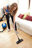 Portrait of a young woman vacuuming — Stock Photo
