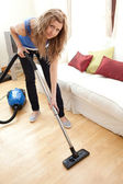 Portrait of a bored woman vacuuming — Stock Photo