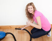 Portrait of a cheerful woman vacuuming — Stock Photo
