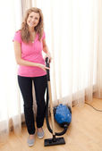 Portrait of a happy woman vacuuming — Stock Photo