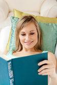 Lächelnde frau, ein buch auf dem sofa liegend zu lesen — Stockfoto