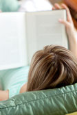 Woman reading a book lying on a sofa — Stock Photo