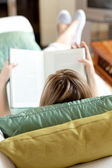 Blond woman reading a book lying on a sofa — Stock Photo
